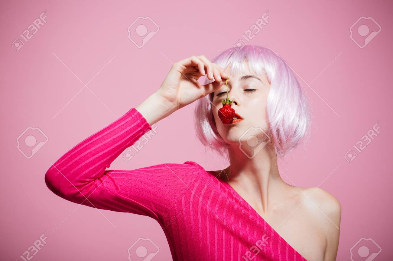 Girl in artificial hair hold red berry in mouth. Fruit and vitamin. Skincare, spa and health. Beauty and fashion. Woman in wig has no makeup on pink background - 92293417