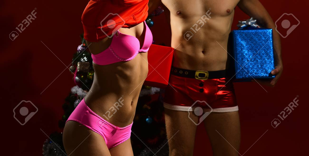 Winter holiday celebration. Couple in love in santa hat, family relations  and erotic. Xmas party and sex games. Christmas man and woman couple at ...