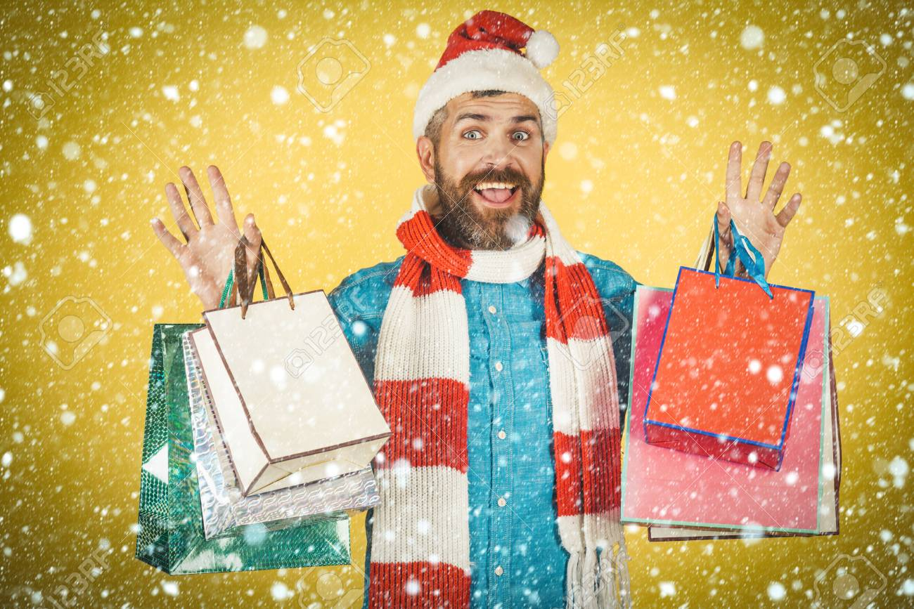 b5d3fb26fbdbb Black friday sale concept. Winter. christmas new year snow concept Christmas  hipster shopper smile in santa hat and scarf. Man
