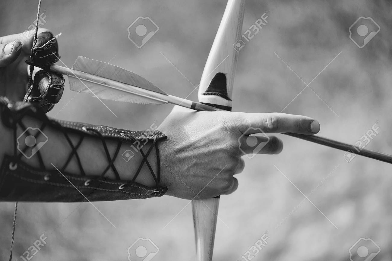 Archer hands with bow shoot arrow with blue and yellow fletchings on natural background - 90679813