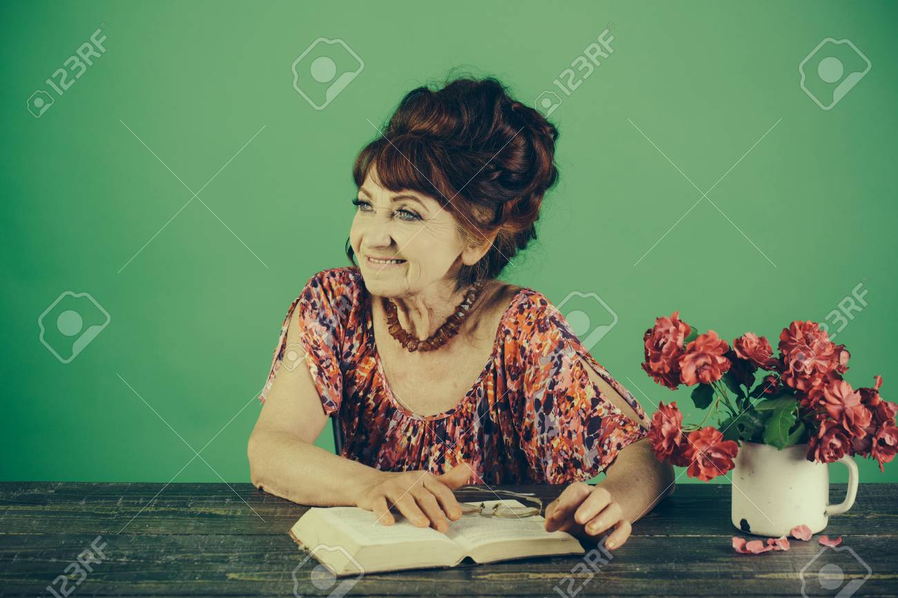 Old woman reading book with glasses at flowers  Pension and retirement,