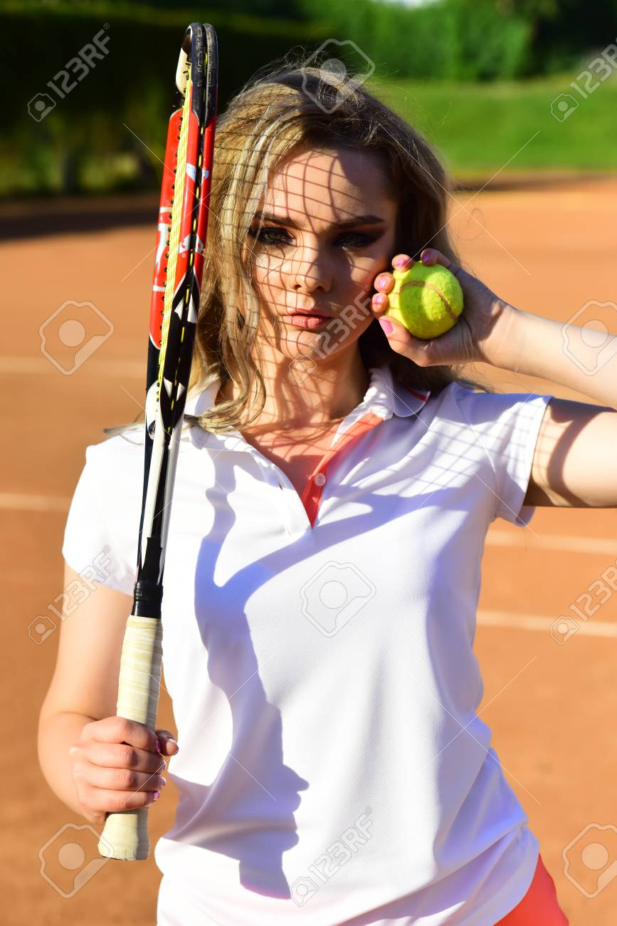 Stock Photo - Woman player with tennis racket and ball on court. Girl with  net shadow on face on sunny day. Fashion 1b8175d28b