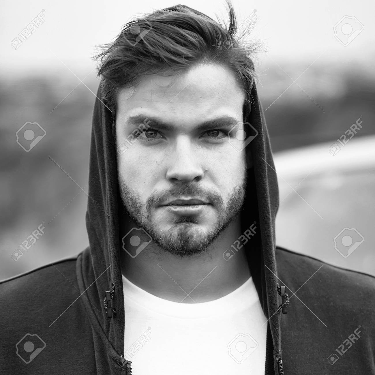 Young man with bearded serious face brown hair and blue eyes..