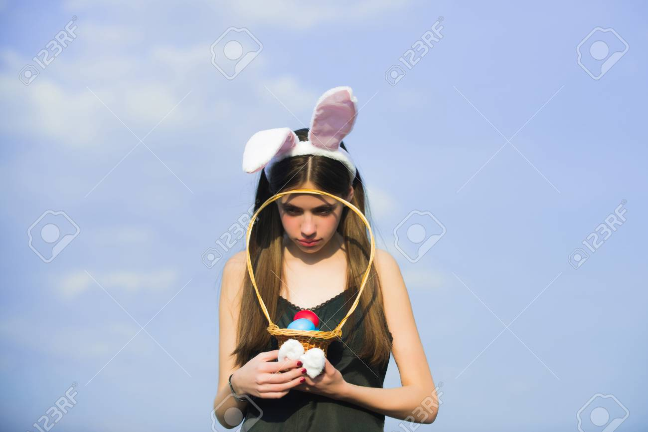 Easter woman holding wicker basket with colored eggs. Unhappy girl with  rosy bunny ears on f10aee56f2c7