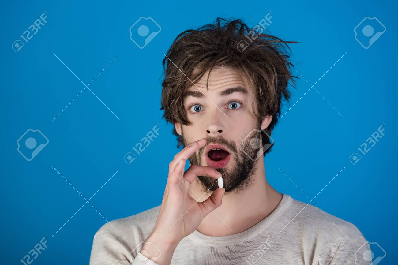 Man with surprised face hold pill. - 95298961