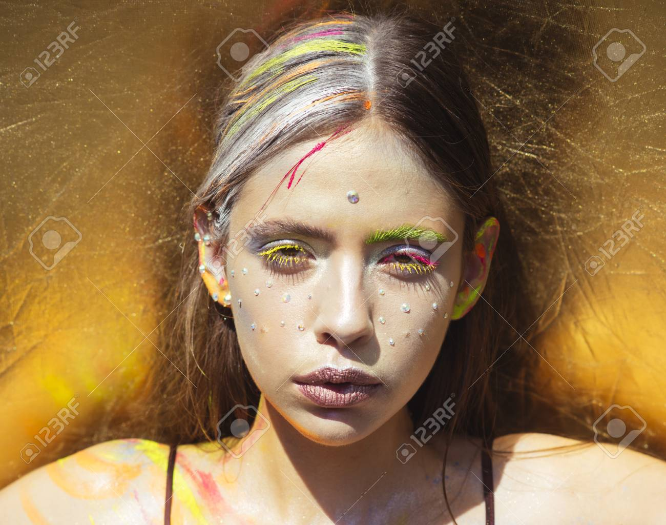 Indian woman with colorful neon paint makeup face. Paint party, colors festival. Holi