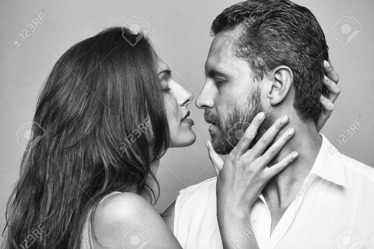 young couple of bearded handsome man with beard and pretty woman or girl with long brunette hair embracing in studio on grey background - 96226935