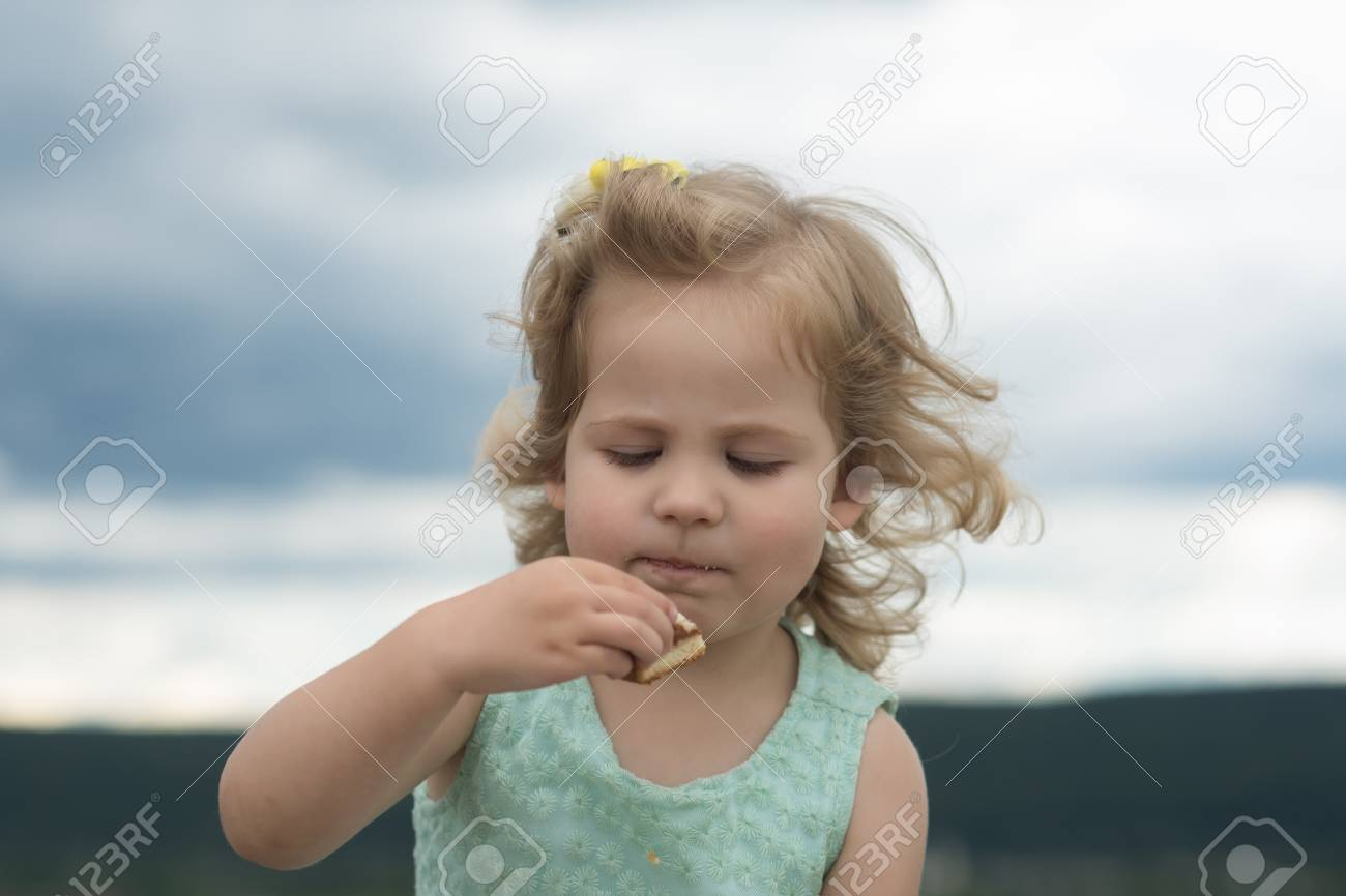 71dd0941b7bb Girl Child Eat Cookie On Summer Day On Cloudy Sky. Food
