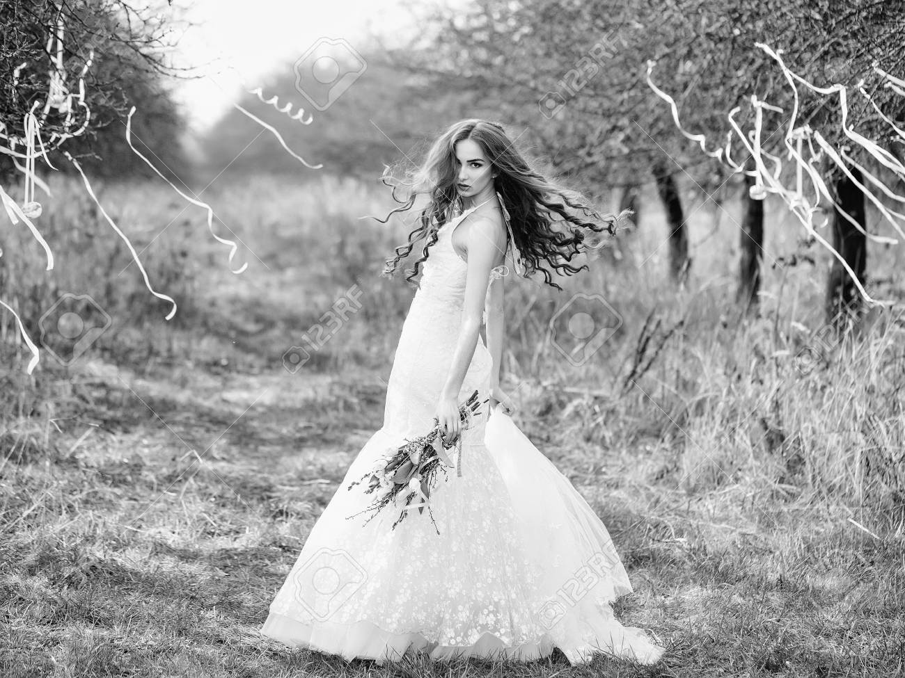 Beautiful Young Bride In White Wedding Dress With Flowers In Stock