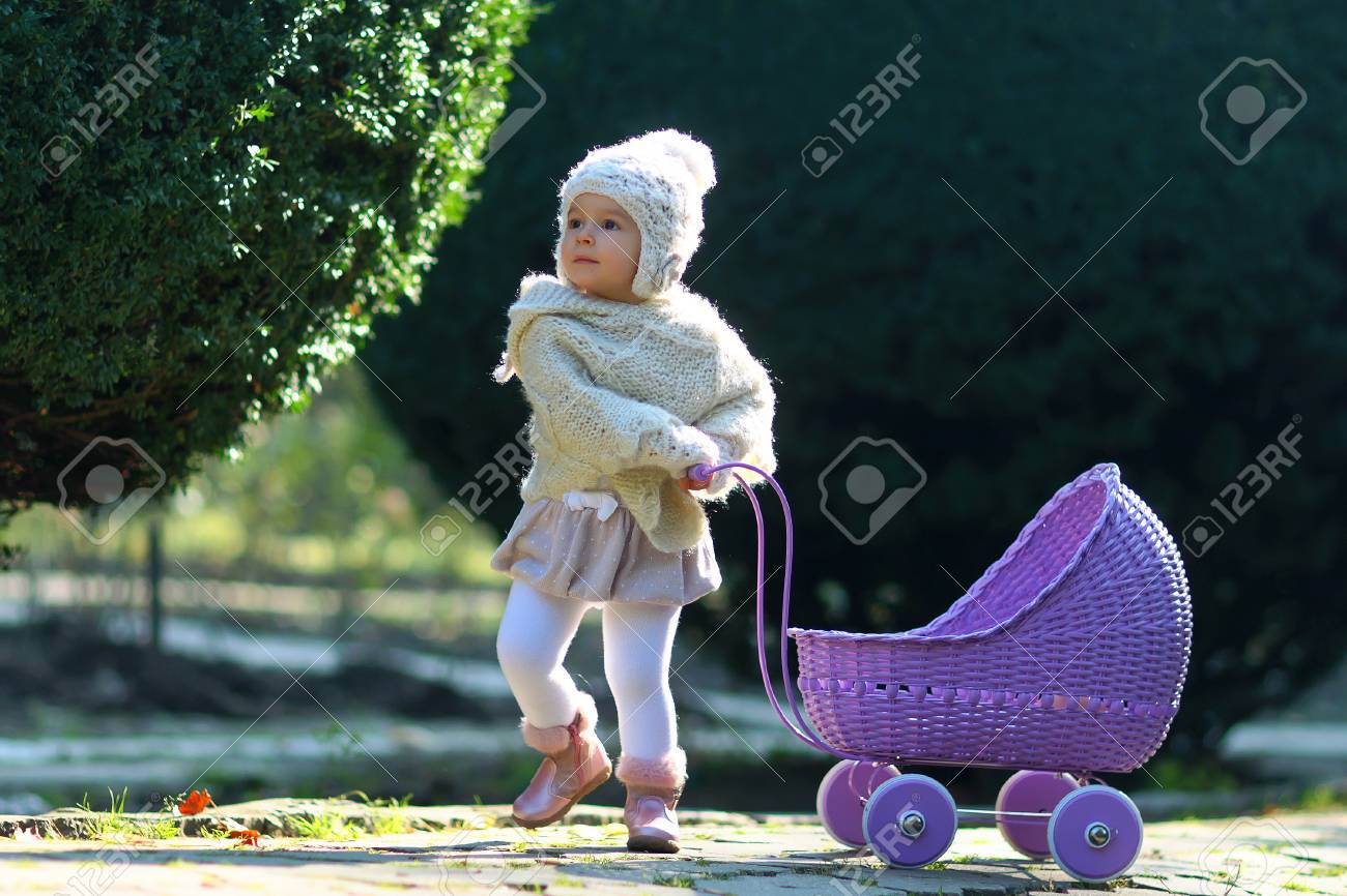 c1623d60b Girl walking with vintage doll stroller on sunny day. Baby rolling violet  toy carriage on