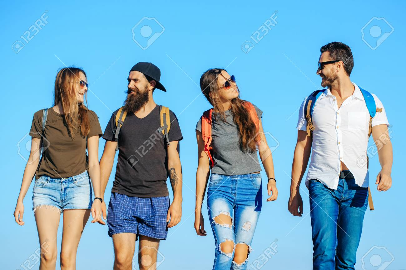 Happy friends on blue sky, wanderlust. Men and women travel on summer  vacation.