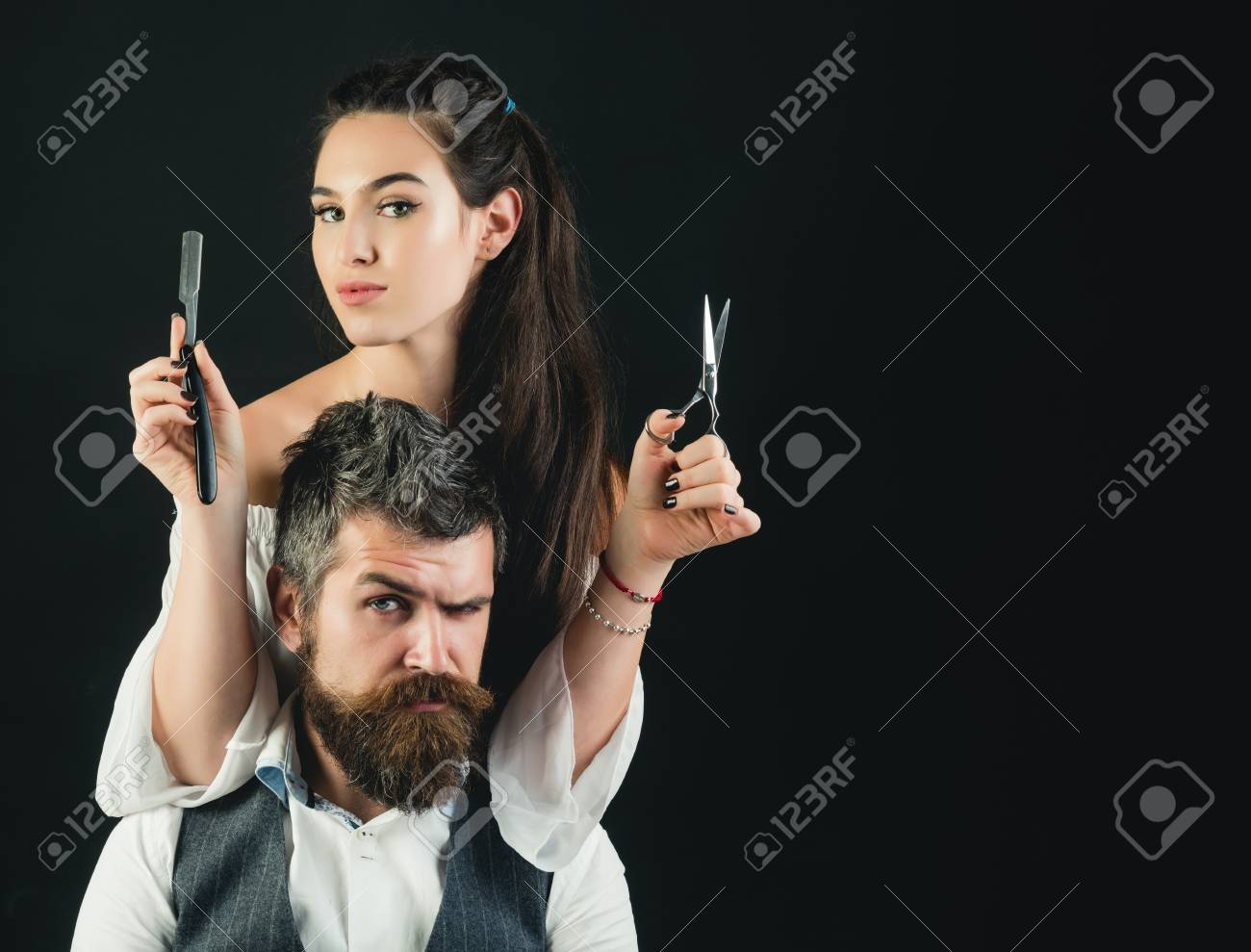Young handsome man with long beard and moustache on serious face with young woman cutting with scissors - 98726253