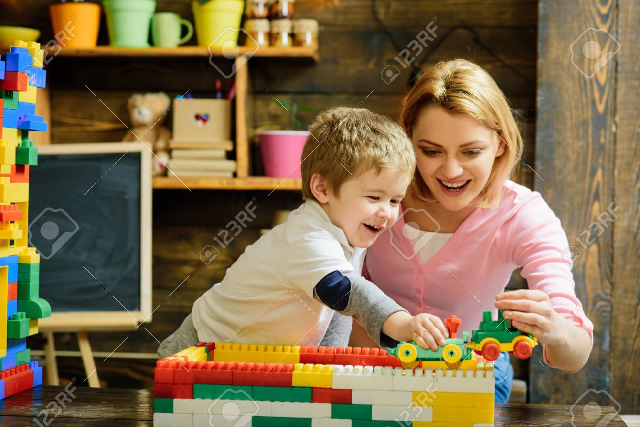 Motherhood concept. Blond mom and son play with plastic building blocks train. Excited preschooler playing with his smiling mother or kindergarten teacher. - 99544730
