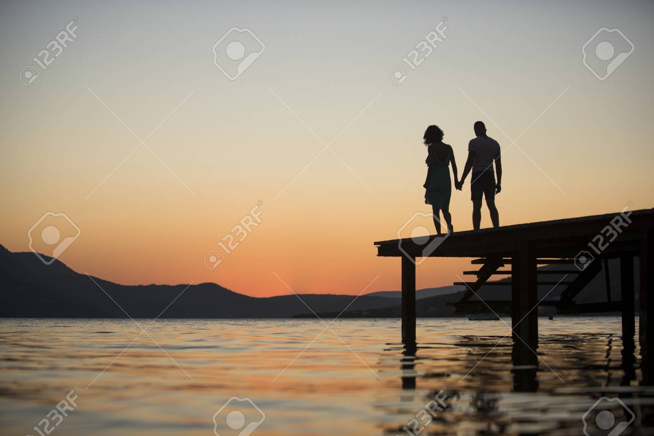 Silhouette of sensual couple stand on pier with sunset above sea surface on background. Couple in love on romantic date in evening at dock, copy space. Romance and love concept. - 99618497