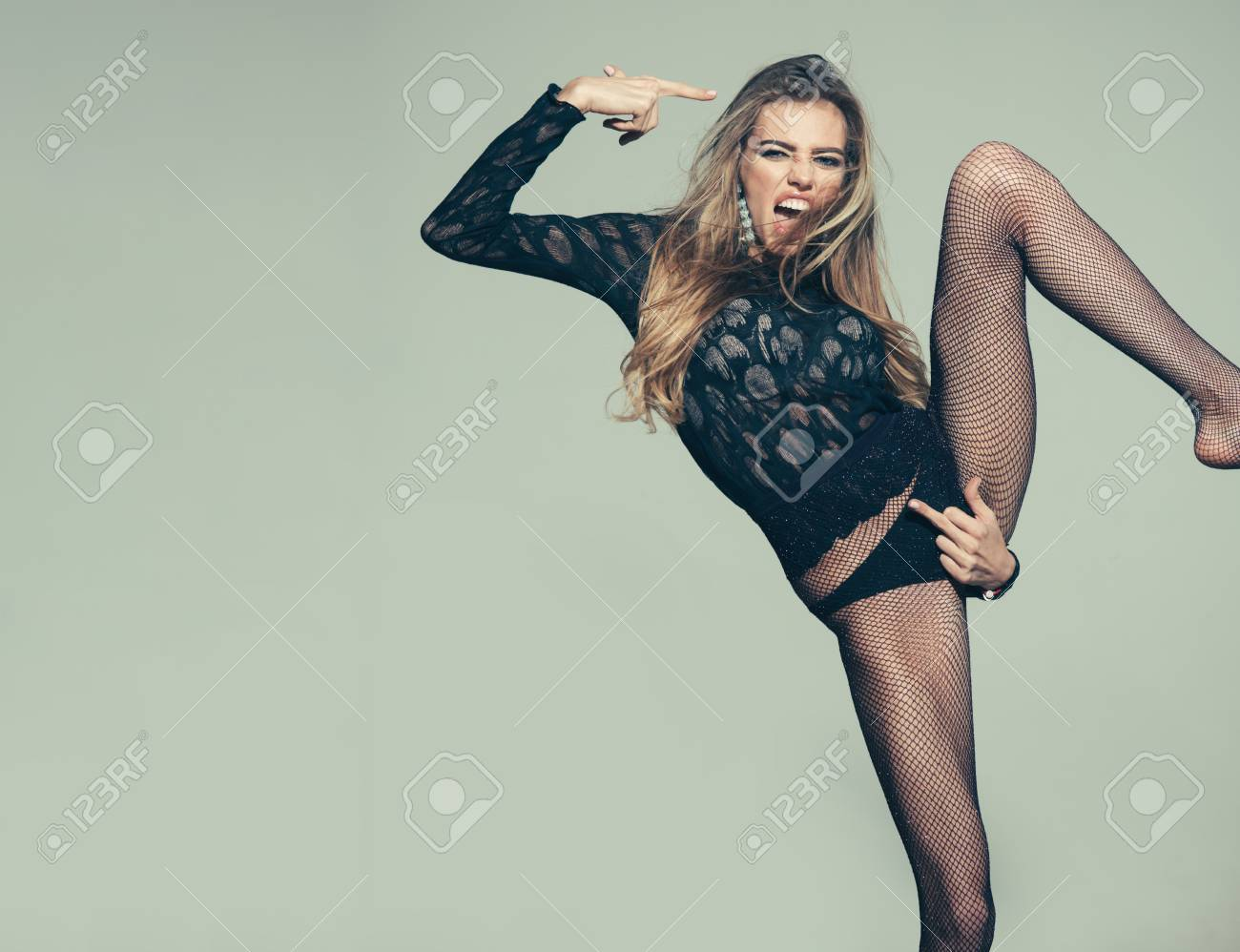 Sexy woman shows fuck gesture on her panties. Obscene concept. Girl in lace  top and underwear, tights in black panties. Hand touching pubis in fuck  gesture.