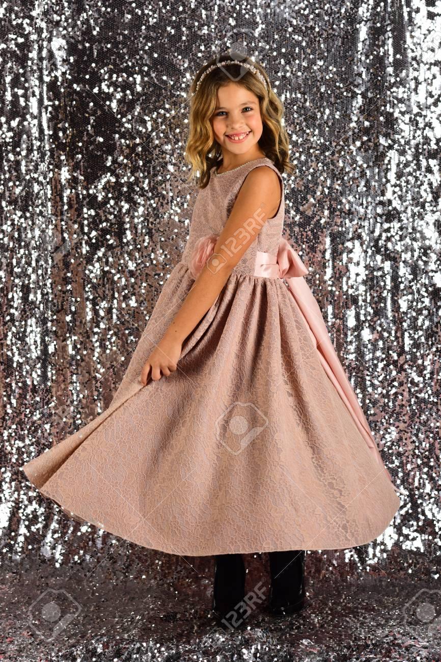 a23fac0e5b91 Child girl in stylish glamour dress, elegance. Fashion model on silver  background, beauty