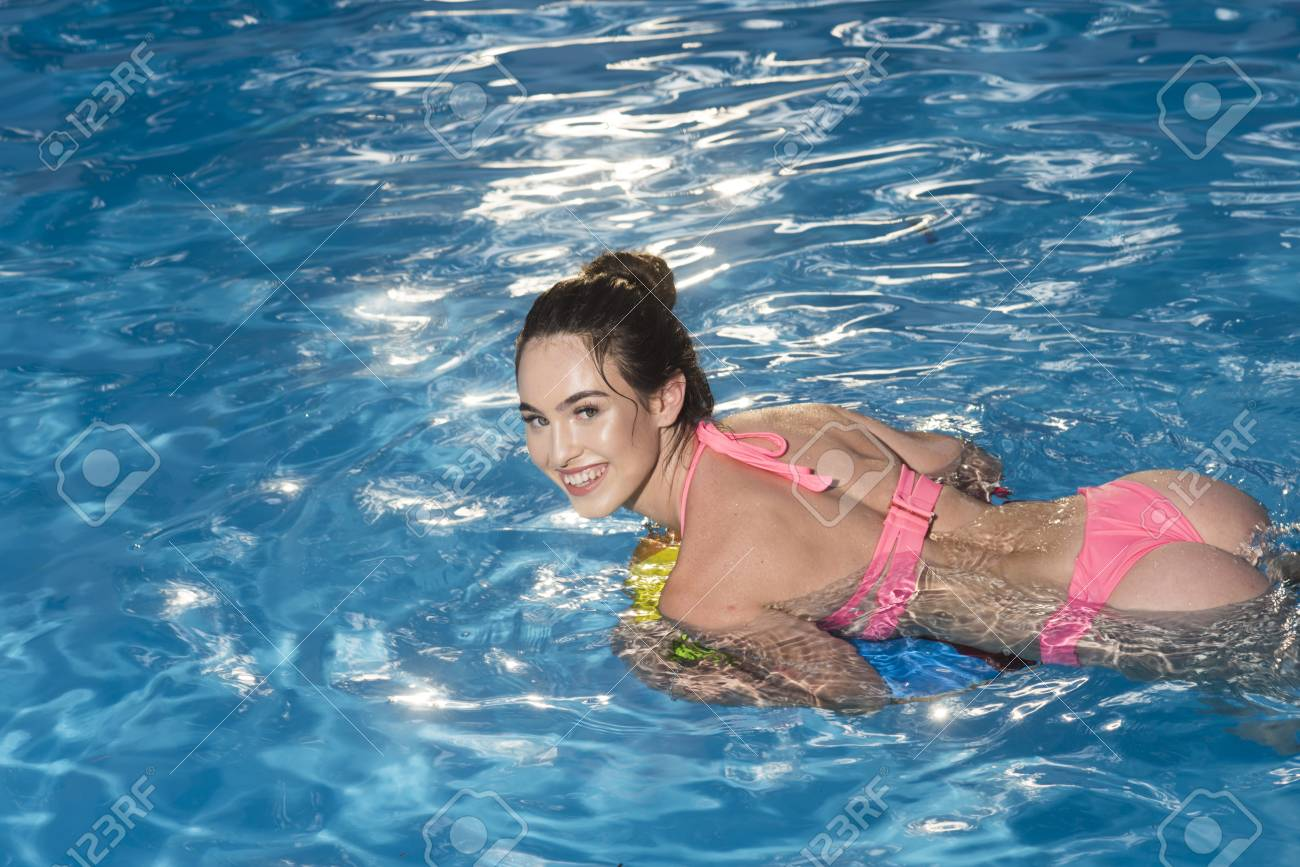 Maldives or Miami beach. Sexy woman on sea with inflatable ring. Fashion and beauty of woman with natural makeup. Relax in spa luxury swimming pool.