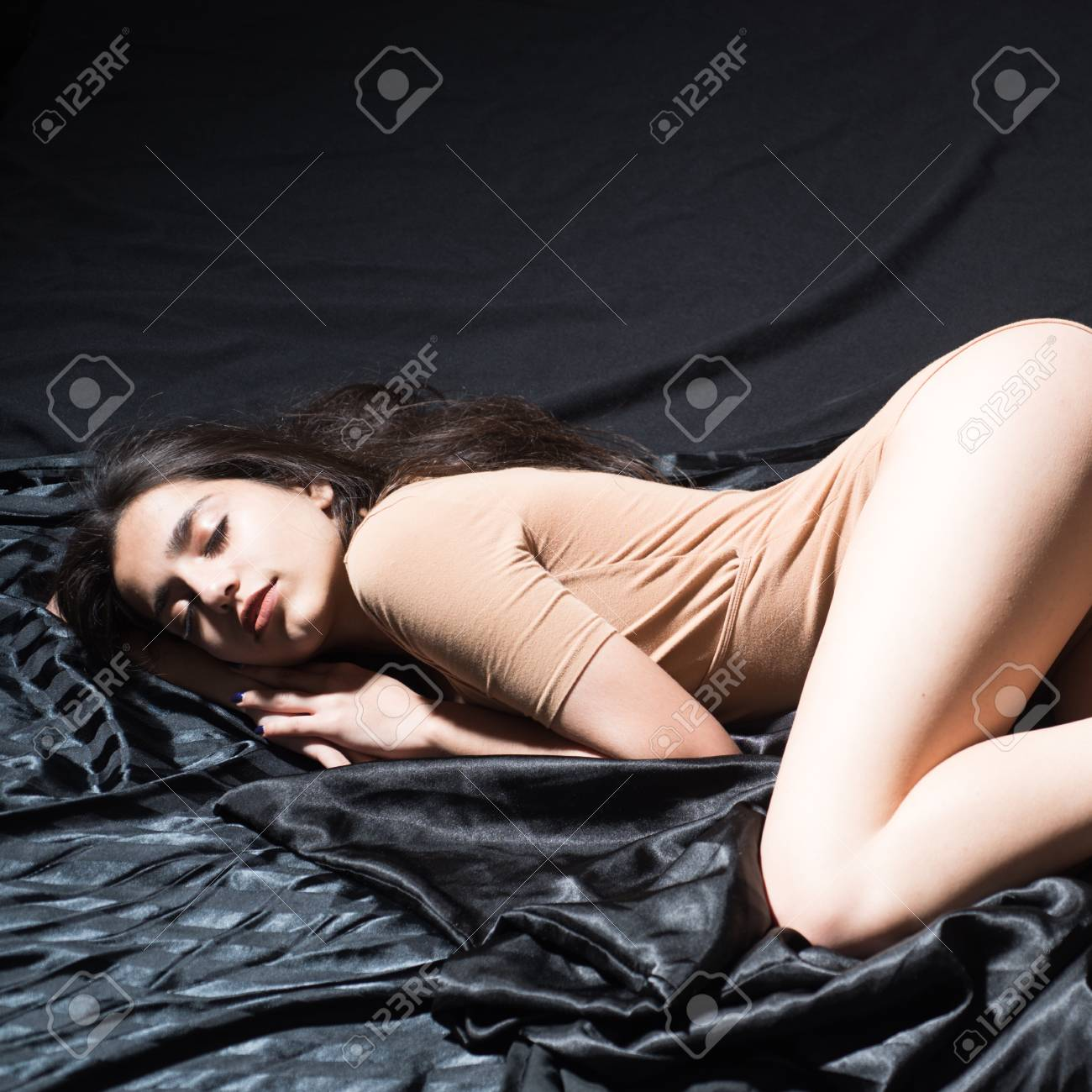 Stock Photo Young Female Lying In Cozy Bed Sexy Girl In Beige Body Suit On Black Background Sensual Girl Falling Asleep Erotic Fantasy Concept