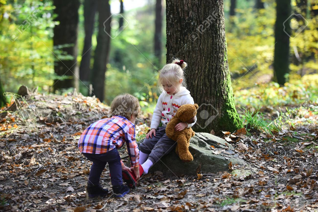 Little boy put shoes on girl feet. Brother help sister to put red boots. Helping hand concept. Children getting ready for walk in autumn forest. Childhood friendship, love and trust - 104394794