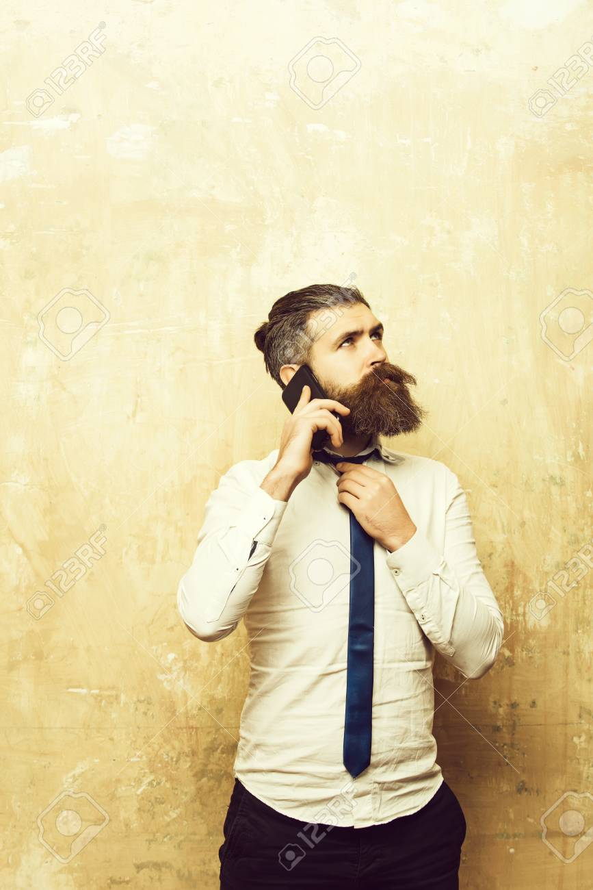 businessman or bearded man with long beard speaking on phone - 112408487