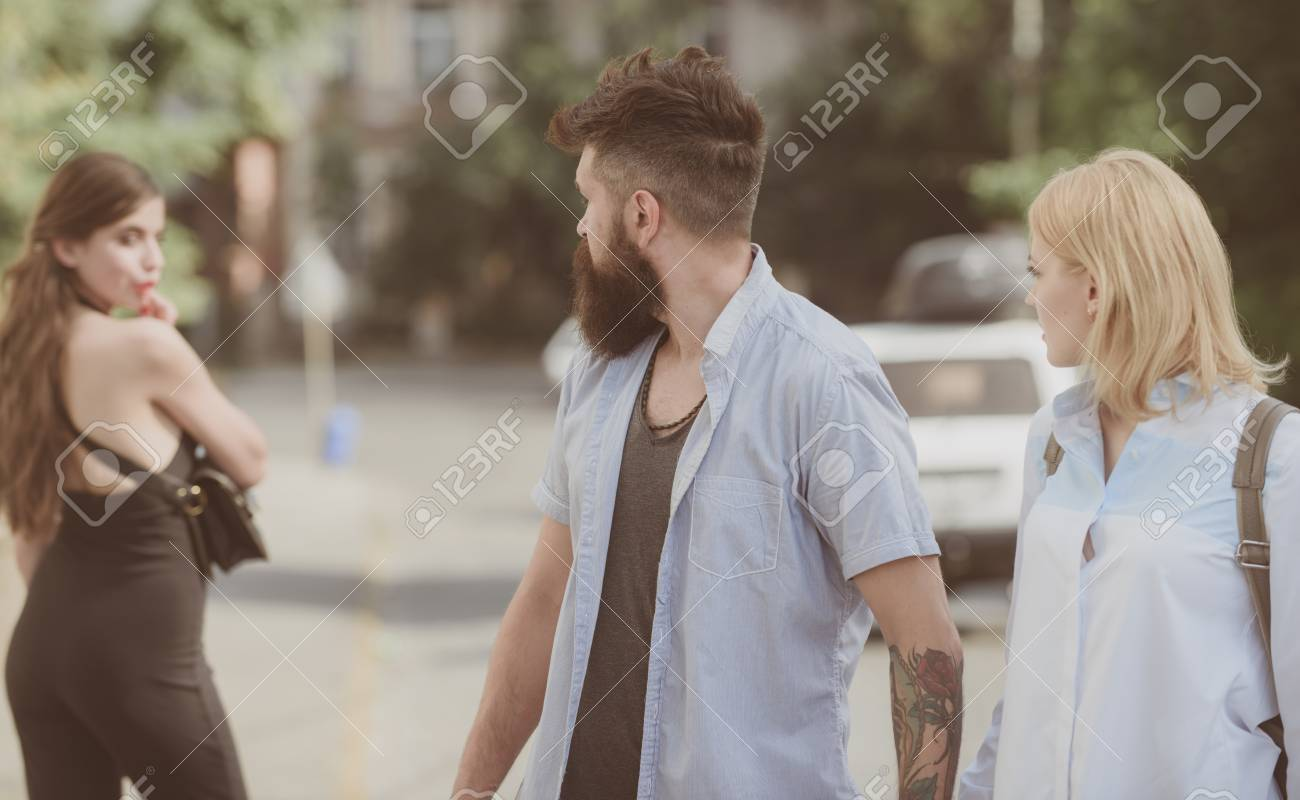 Relationship problem. Man cheating his wife or girlfriend. Bearded man looking at other girl. Hipster choosing between two women. Betrayal and infidelity. Unfaithful love. Love triangle and threesome. - 116280841