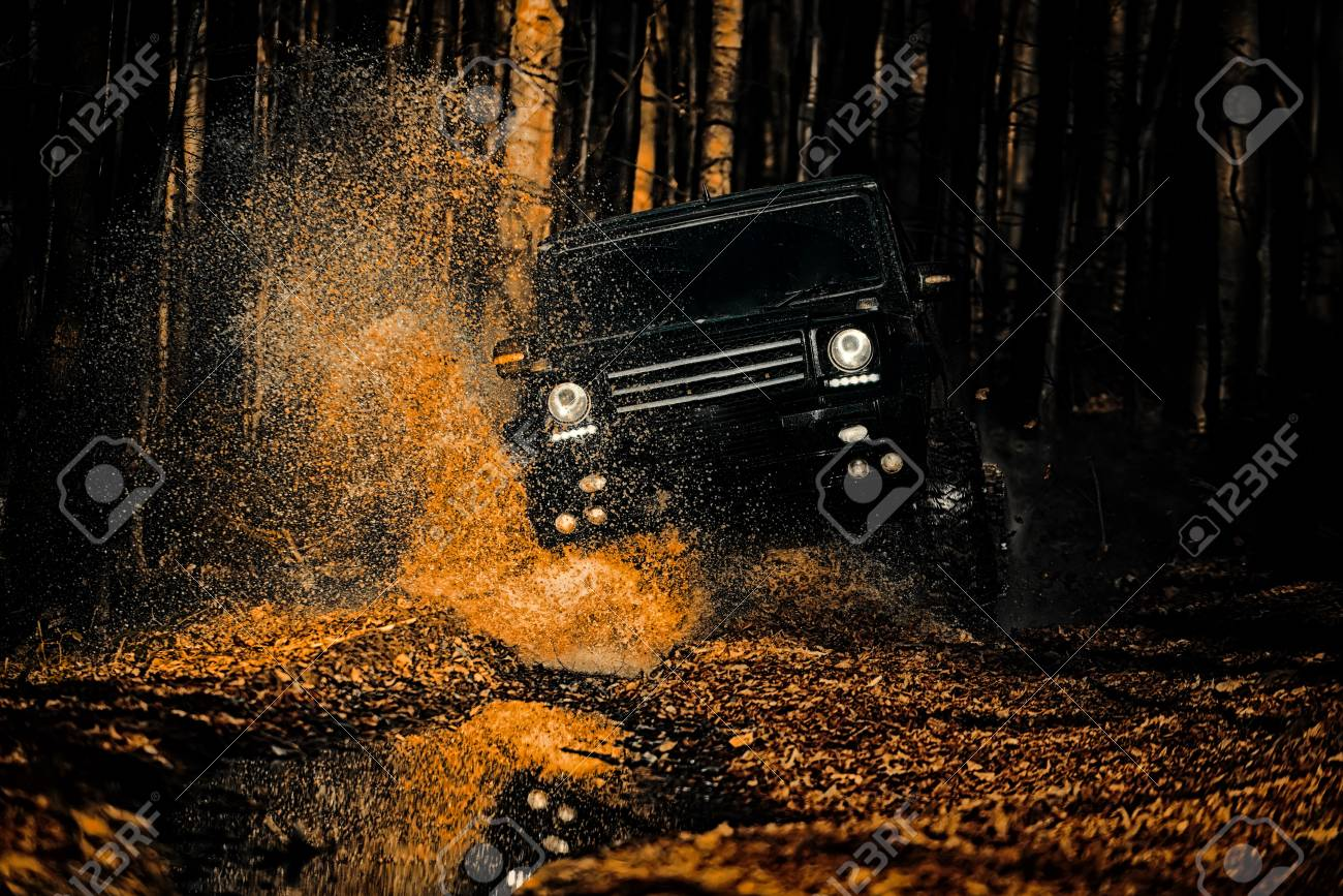 Off-road vehicle goes on the mountain. Mud and water splash in off-road racing. Drag racing car burns rubber. Extreme. Off-road car. Best Off Road Vehicles. Rally racing. - 119759925