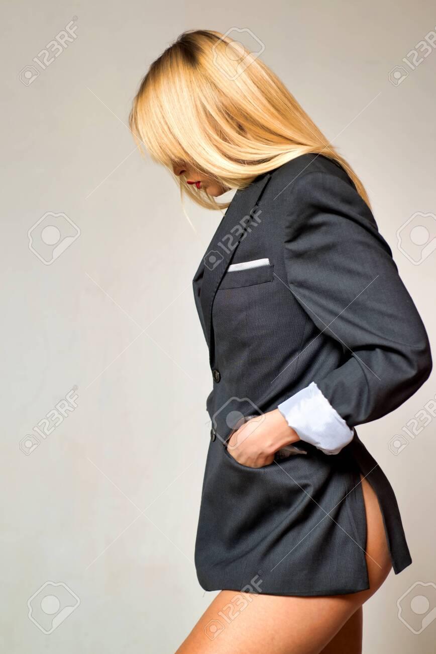 Sexy female receptionist. Attractive blonde with legs in mans jacket. Sexy school uniform. - 124924787
