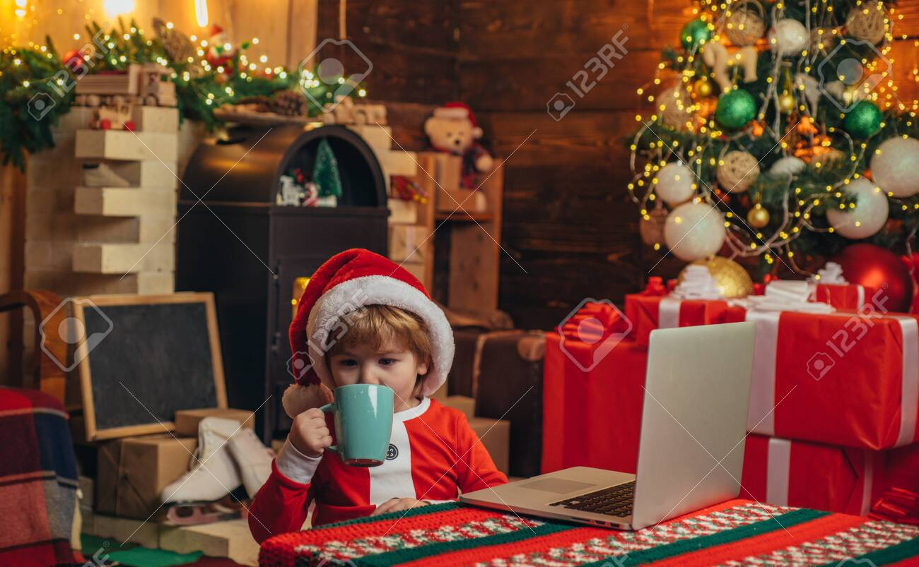 Boy Child With Laptop Near Christmas Tree Buy Christmas Gifts Stock Photo Picture And Royalty Free Image Image 126651072