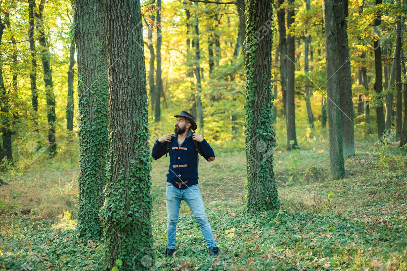 Portrait of handsome man walking outdoors. Man with leaves outdoor. Handsome man walking in the Park and enjoying the beautiful autumn nature. - 128605046