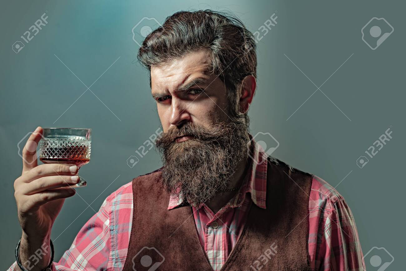 Hipster with beard and mustache in suit drinks alcohol after working day. Man or businessman drinks whiskey on black background. - 132071182