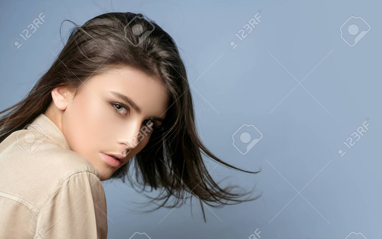 Sensual model girl with smooth skin and makeup. Cheerful happy young beautiful girl. Female fasion. Portrait of serious desire woman. Portrait of a beautiful woman in a white blouse. Grey background. - 134790009