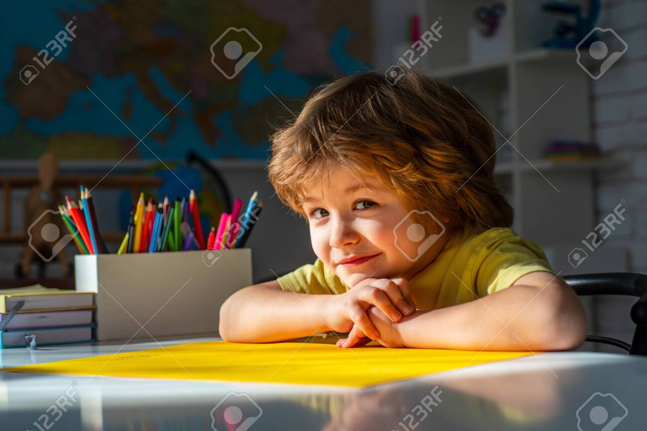 Educational process. Cute pupil with funny face schooling work. Cute little preschool kid boy with teacher study in a classroom. - 143067335
