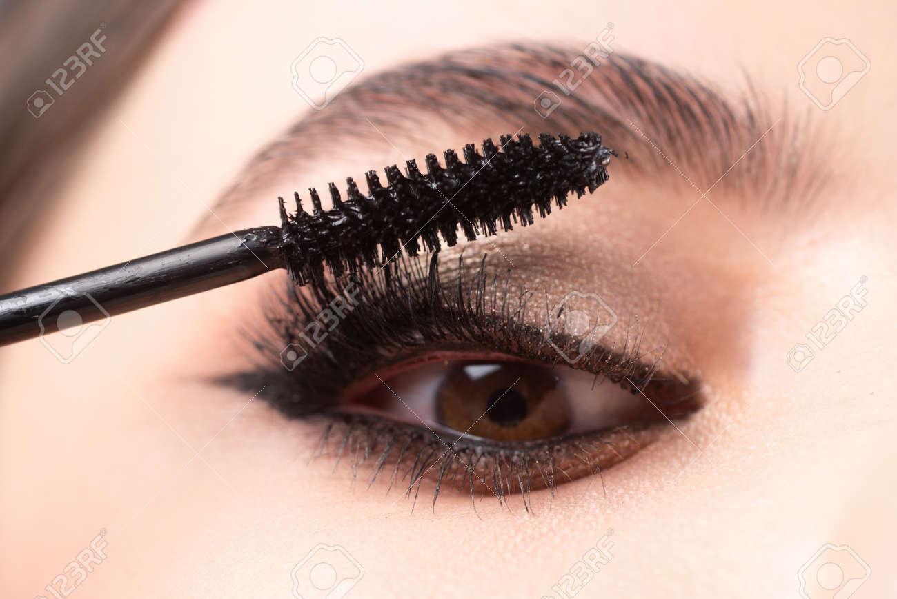 Closeup of eye makeup. Applying maskara on lushes Young woman getting make up with brush. Eyes visage woman. - 165413869