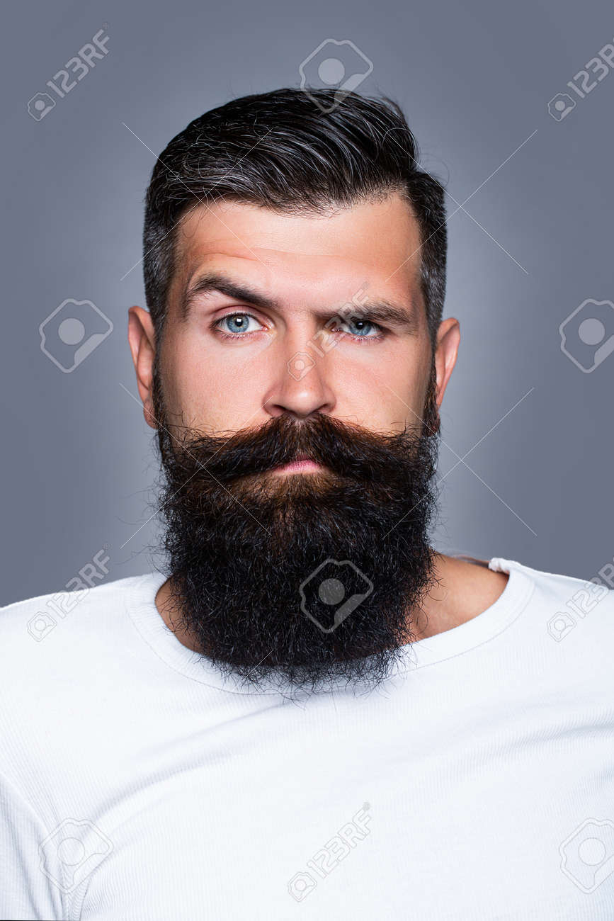 Handsome bearded man with long lush beard and moustacheon grey background. - 165965975
