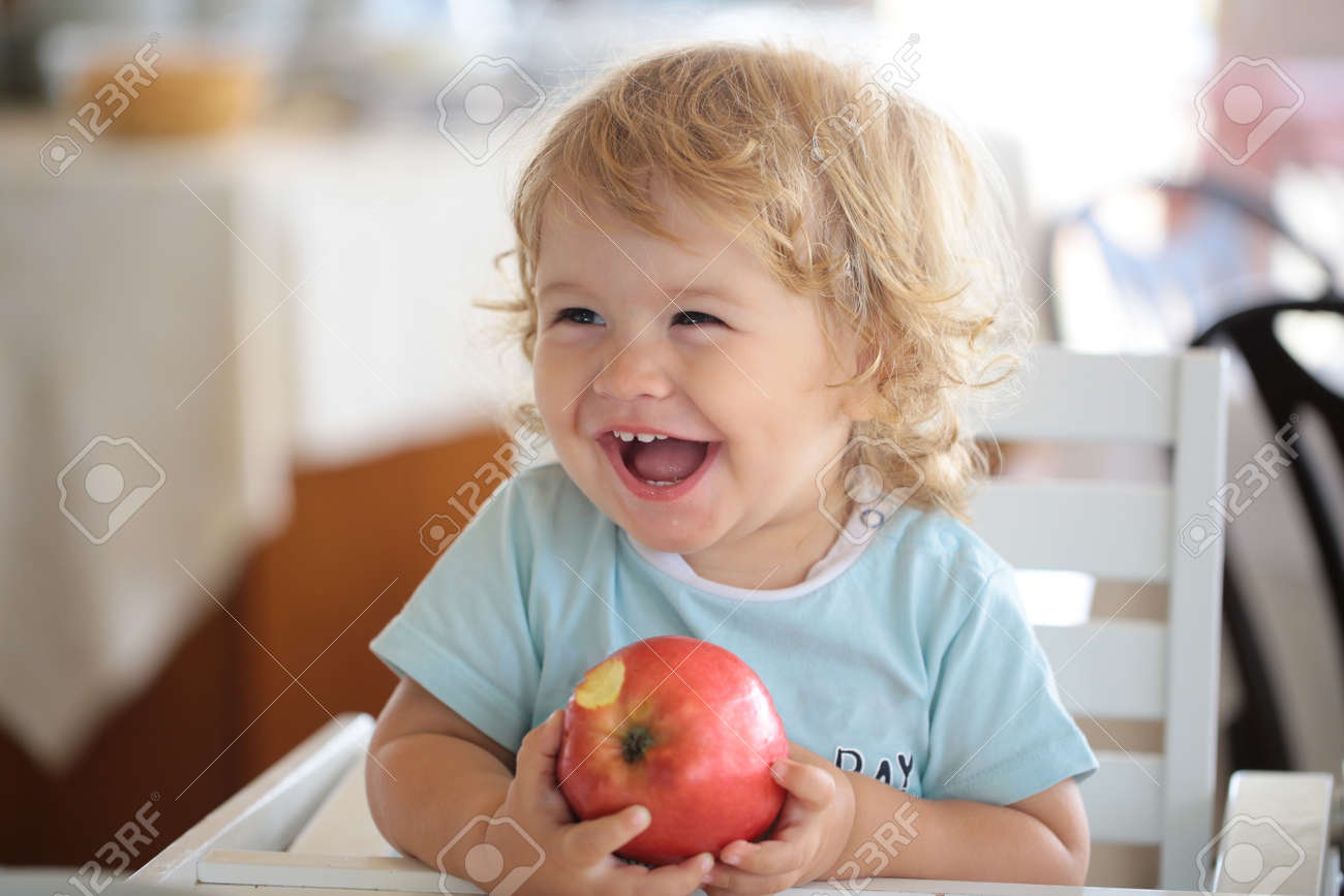Laughing cute child eating apple. Cute baby eat apples. Portrait of cute smiling laughing Caucasian child kid sitting in high chair eating apple fruit. - 166338661