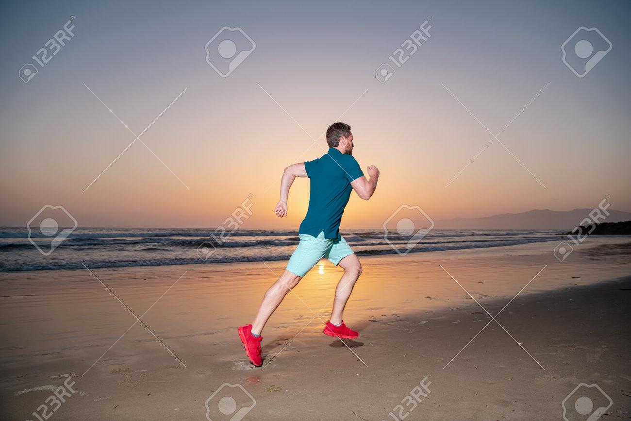 Man running on the beach at sunset. Man runner jogger running. - 168901892