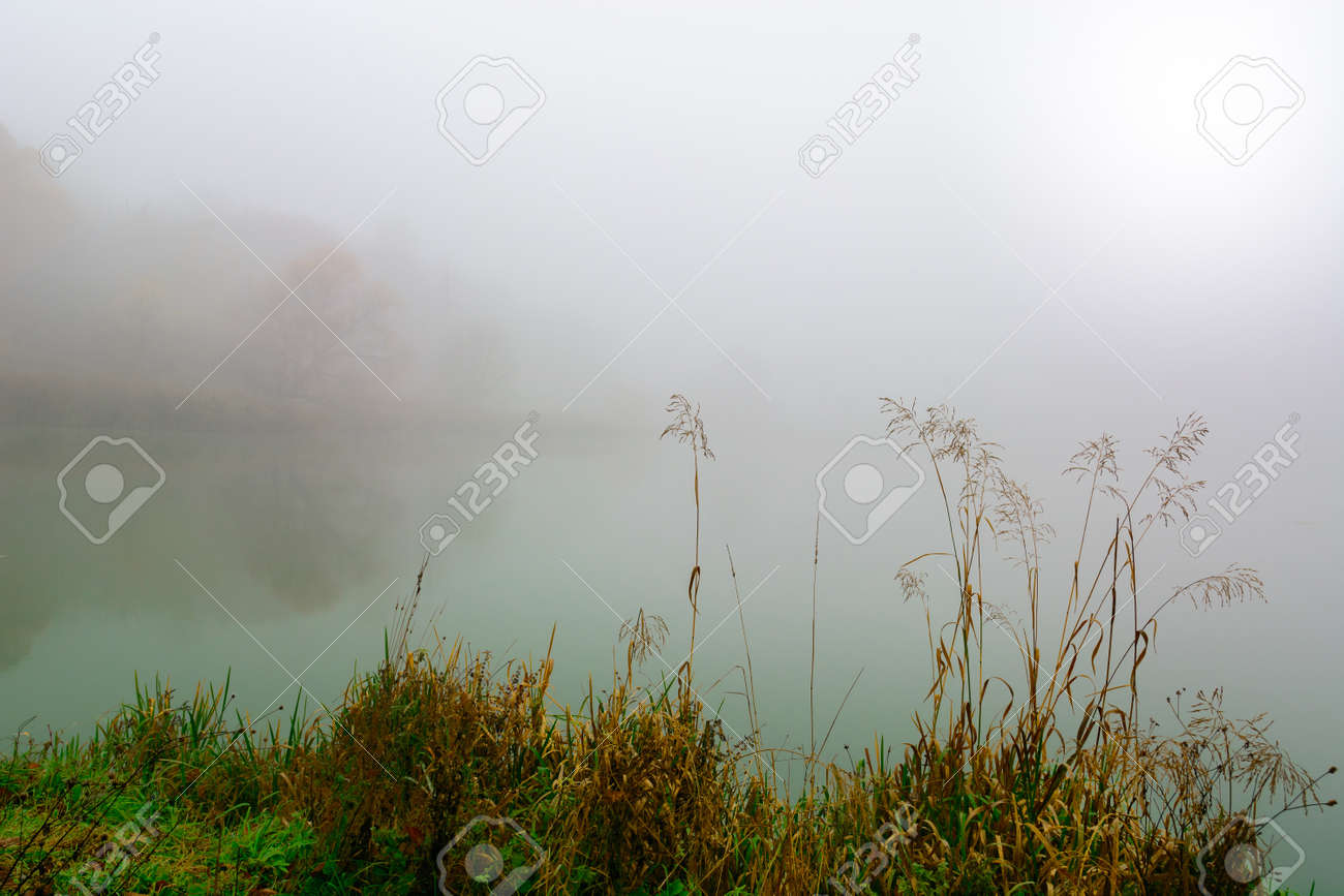 Morning fog on the lake in the fall. Mystical and mysterious weather. Gray autumn natural background. - 132787916