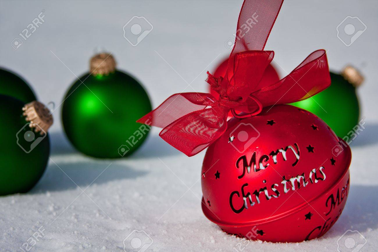 merry christmas jingle bell with green ornaments in the snow stock