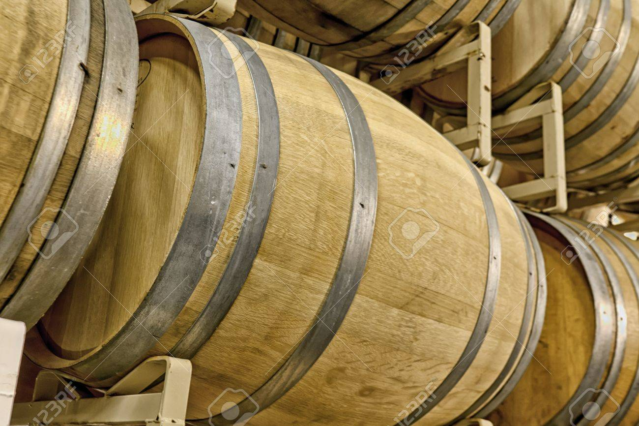 oak wine barrels. racks of oak wine barrels in cave stock photo 15235549