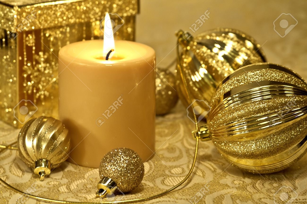 Christmas Gold Decorations With Lighted Candle On Table Stock Photo ...