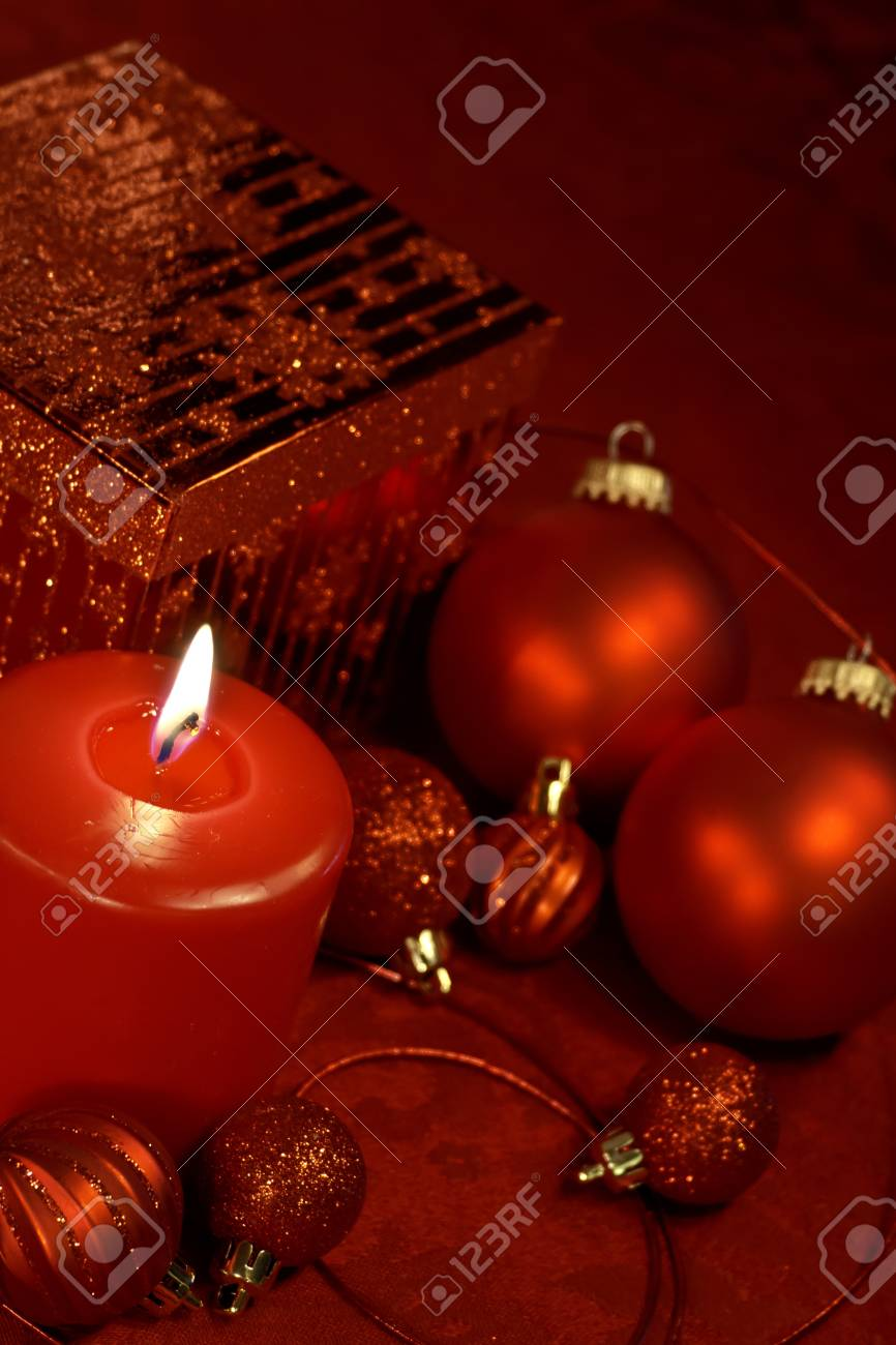 Festive holiday table decorated in red Christmas ornaments, present and lighted candle Stock Photo - 16510063