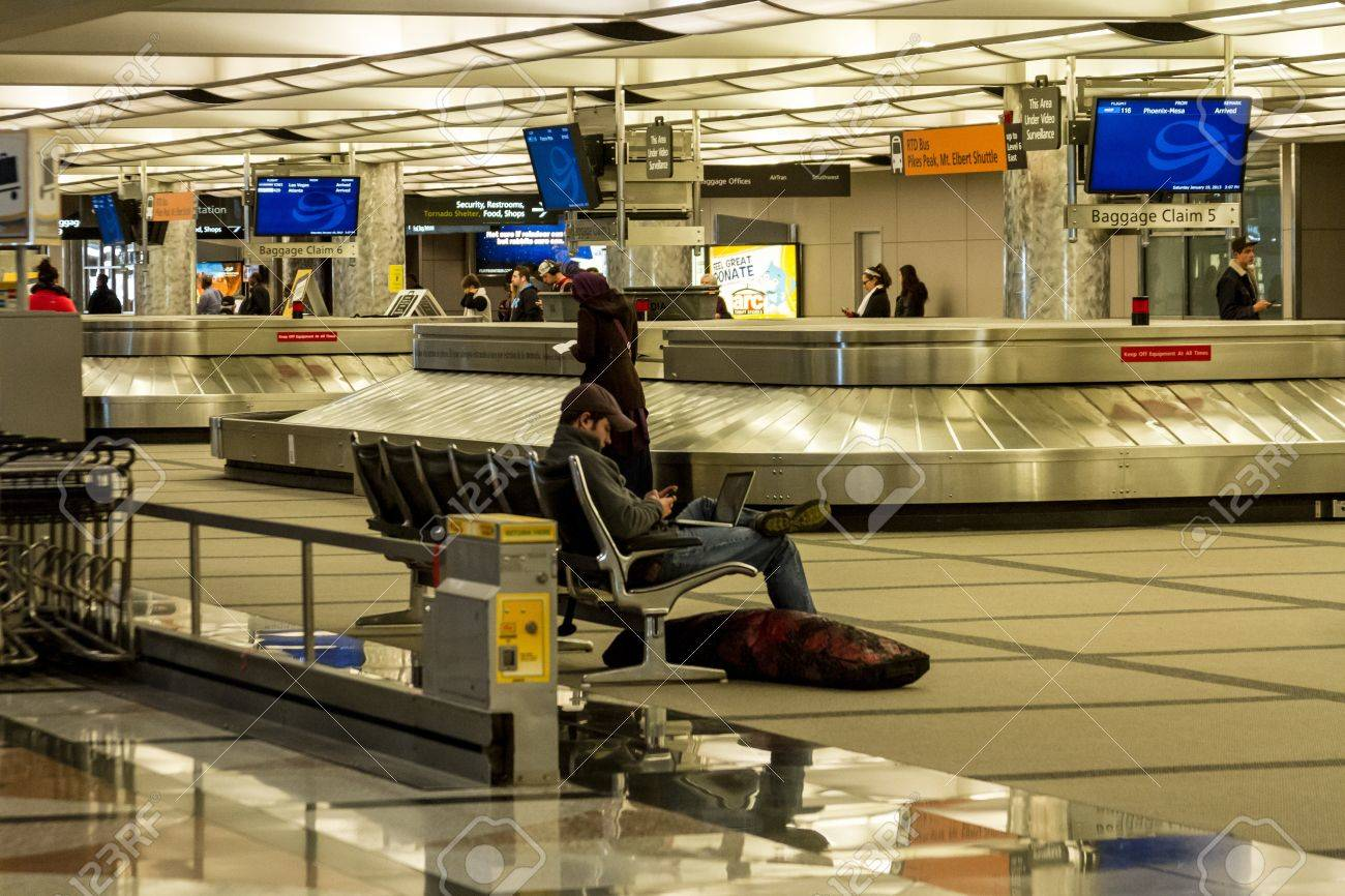 Man on computer and phone waiting at baggage claim in airport Stock Photo - 17435515