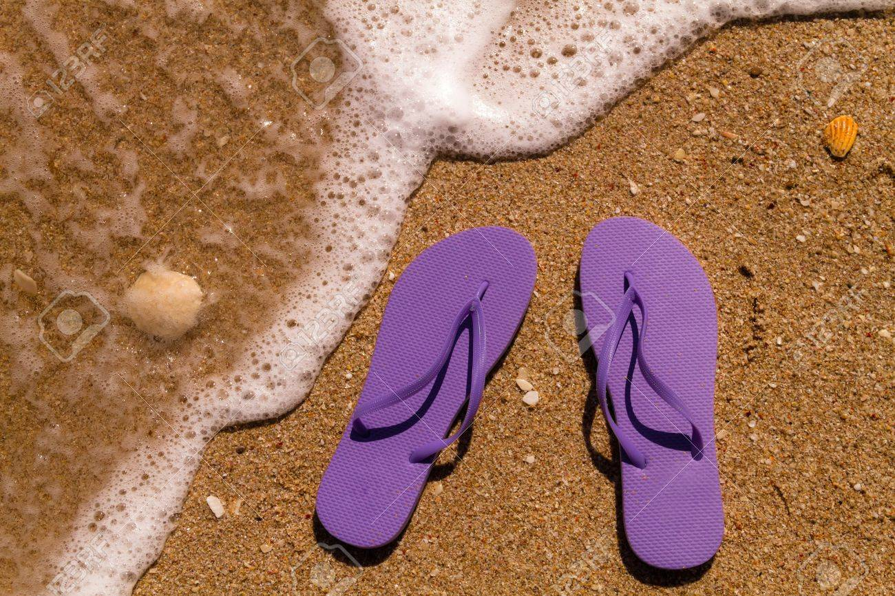 ef69ecb7cc7a Pair of purple flip flops laying on the sand with ocean wave washing up on  the