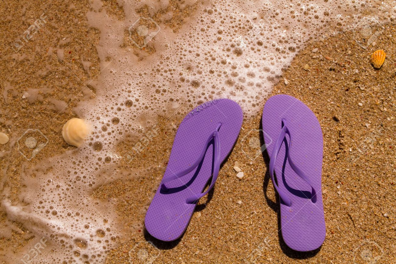 b93fe3529ce8 Purple flip flops laying on the sand with ocean water washing up on shore  and sea