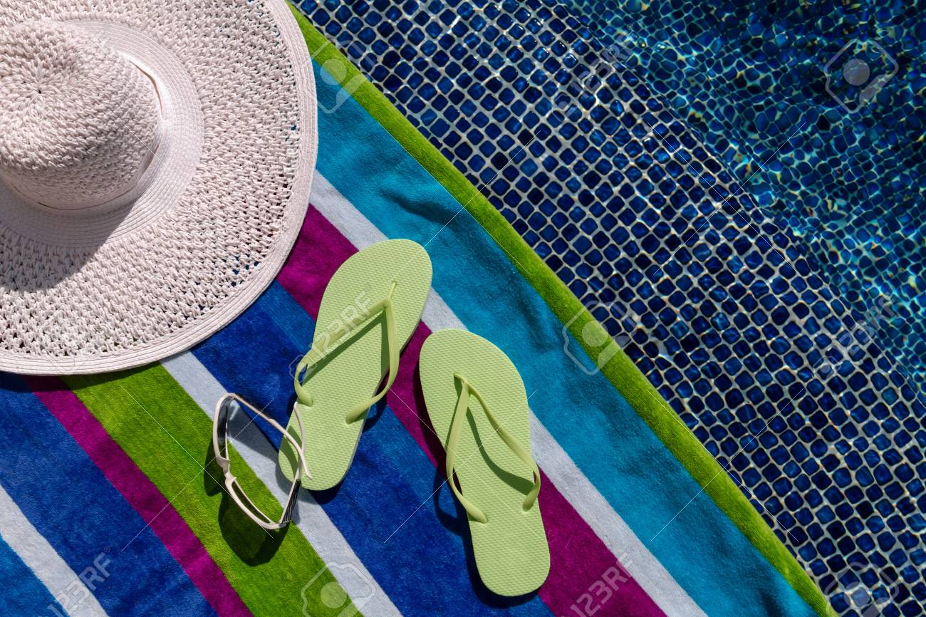 Pair of green flip flops by the pool on a bright blue, green, purple and white striped towel with sunglasses and big white floppy hat Stock Photo - 18837926