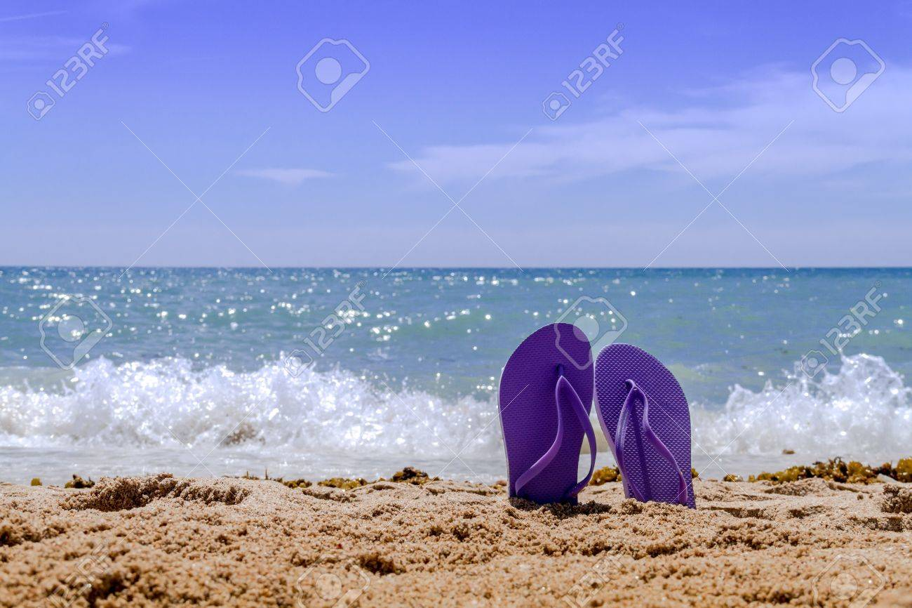 Purple pair flip flops sticking up on a sandy beach with water and waves crashing on the beach Stock Photo - 18964269