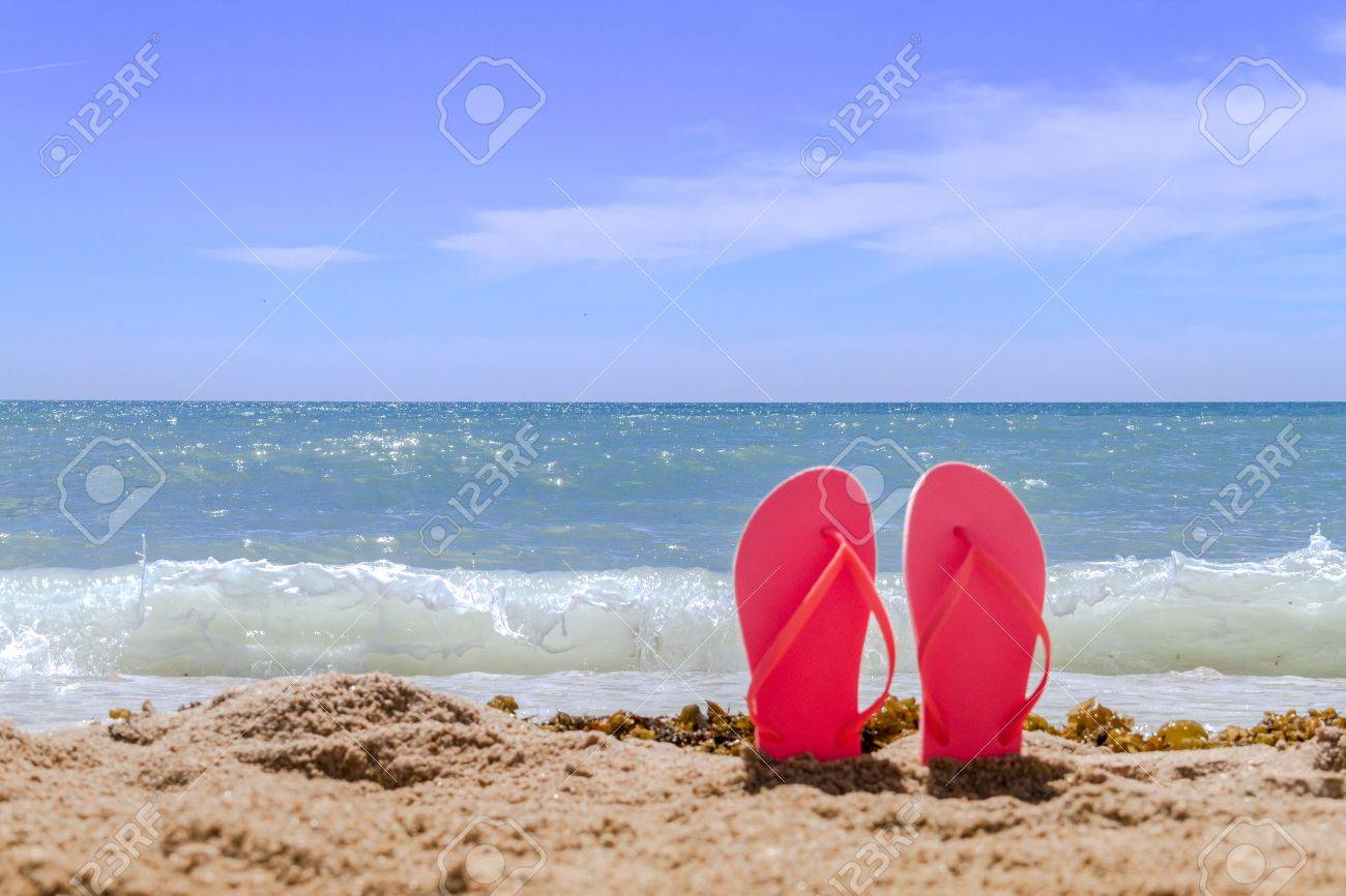Orange pair flip flops sticking up on a sandy beach with water and waves crashing on the beach Stock Photo - 18964256