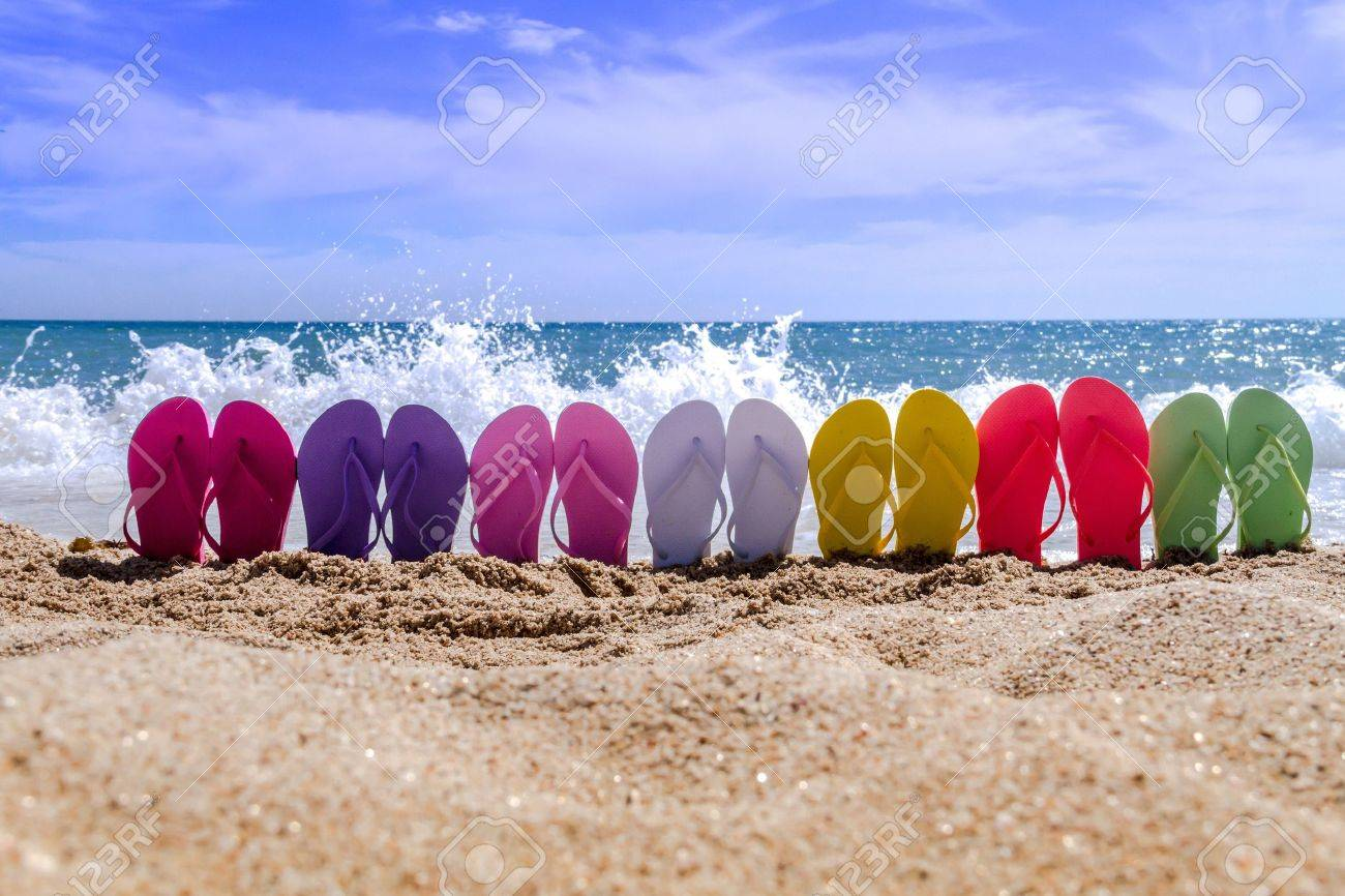 Line of brightly colored flip flops arranged in a rainbow on beach with large waves breaking on sandy shore Stock Photo - 18964277