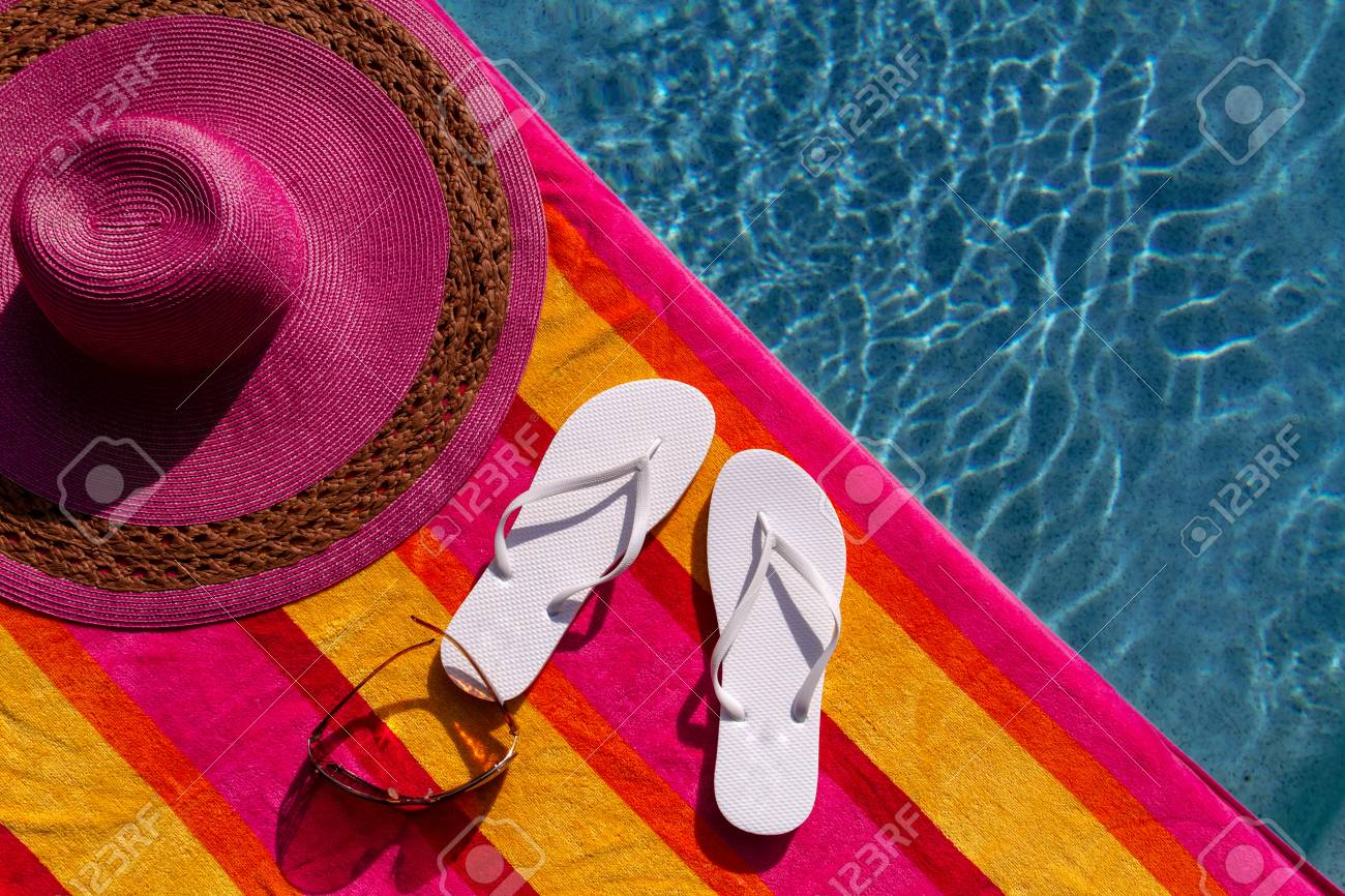 47e733a9 ... big pink floppy hat. Pair of white flip flops by the pool on a bright  orange, pink, red