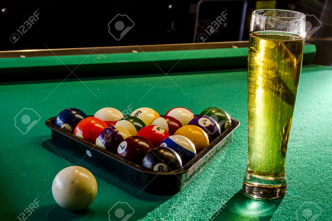 Colorful Billiard Balls In Triangle Rack With Cue Ball Sitting On Pool Table  With Glass Of